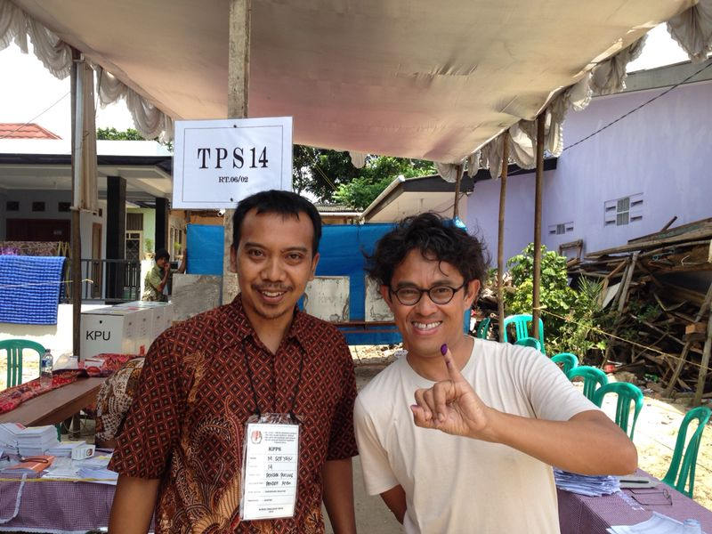 Film director Riri Riza (right) proudly displays his inked finger as evidence of his vote